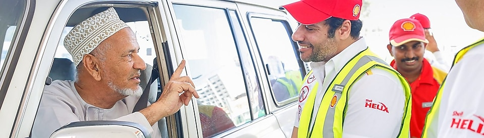 Shell helix attendants talking to a customer in a car