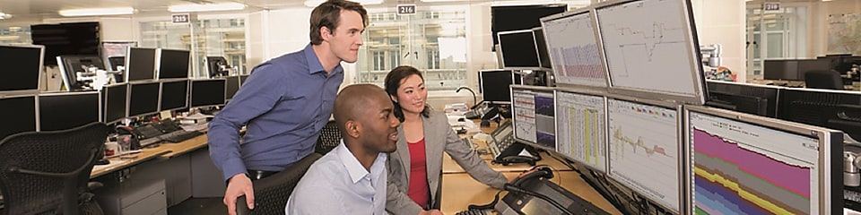 Staff on the Trading Floor examine data on multi computer screens